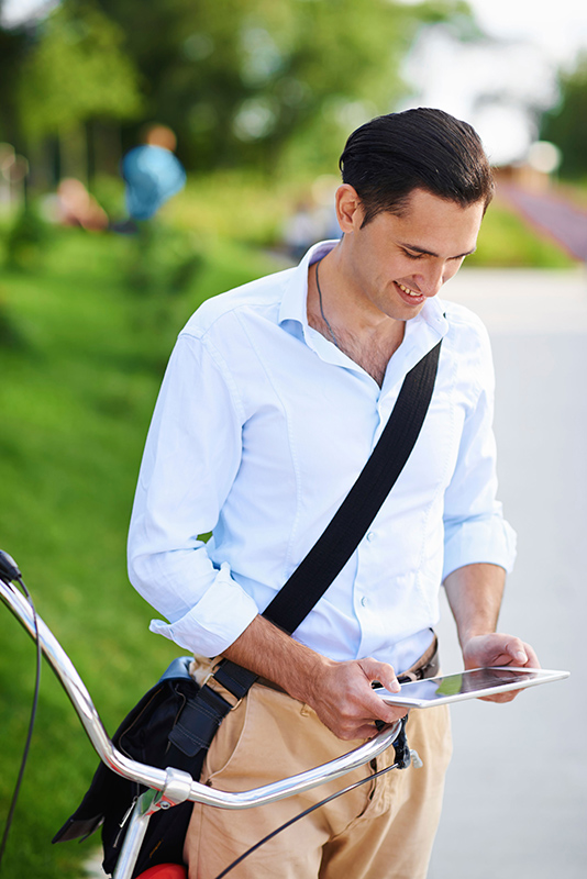 Young professional man with bike consults his tablet.